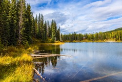 Smooth water reflects the cloudy sky. Rocky Mountains of Canada. Quiet shallow lake surrounded by forest and yellow autumn grass. The concept of ecological, active and photo tourism