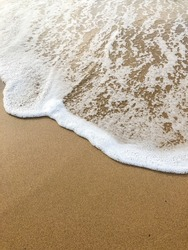 smooth waves of the sea on the sandy beach in summer