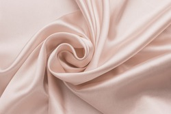 Smooth wrinkled silk bedsheet, fabric background. Abstract crumpled satin texture. Cream color. Folded cloth, wallpaper. Soft wavy pastel beige material, pink glossy textile.