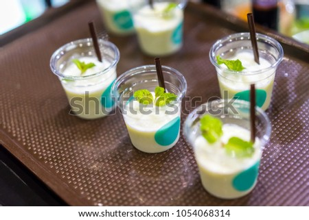 Smoothie beverage sample for refreshing concept in transparent tasting cup on brown tray. Marketing promotion for new launched flavor.