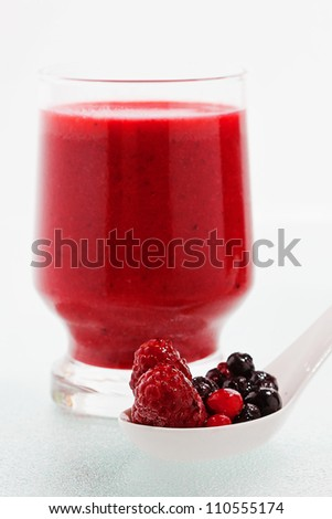 smoothie from mixed berries and spoon with berries in front - stock photo