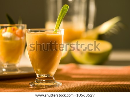 smoothie from tropical fruit in glass, dessert, mixer and various fruit in background