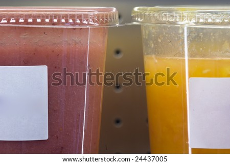 Smoothie in plastic transparent glasses displayed in a shop.copy space left.