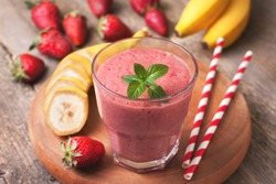 smoothie with banana and strawberry in the glass, fresh strawberries and bananas on the old wooden background