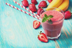 smoothie with banana and strawberry in the glass, fresh strawberries and bananas on the  wooden background (toning)