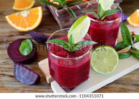 Smoothie with beet and orange in a glass decorated with mint and a slice of lime