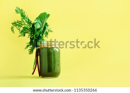 Smoothie with beet greens and carrot tops on yellow background, copy space. Summer vegan food concept. Healthy detox eating, alkaline diet. Fresh squeezed juice, drink from vegetables. Leafy greens