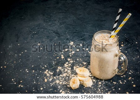 Smoothies with yogurt, banana and oatmeal in a mason jar. On a dark gray concrete stone background, with ingredients for cooking. Copy space