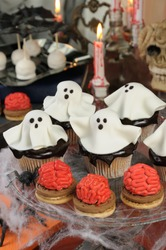 Smorgasbord of biscuit with brains and cupcakes in chocolate glaze decorated marzipan ghosts on Halloween