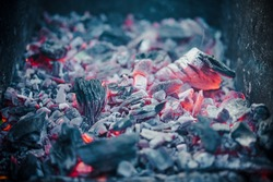 Smouldering coals in a brazier at night. Decaying charcoal, barbeque season