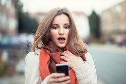SMS. Closeup portrait funny shocked anxious scared young girl looking at phone seeing bad news photos message with disgusting emotion on face isolated cityscape background. Human reaction, expression