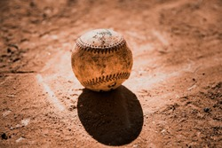 Smudged baseball laying on dirt