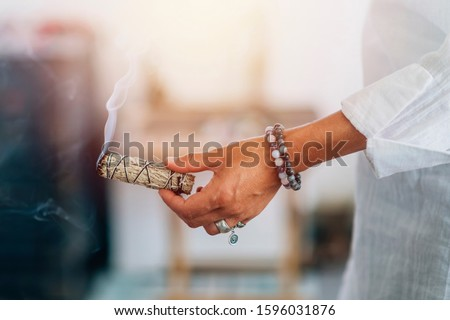Smudging - Hands of a spiritual woman holding burning smoking sage smudge stick