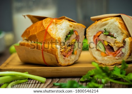 Snack at break time. Famous Vietnamese food is Banh mi thit and black coffee, popular street food from bread stuffed with raw material: pork, ham, pate, egg and fresh herbs.Typical Vietnamese sandwich