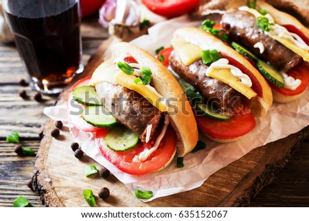 Snack, fast food, hot dogs with Bavarian hunting sausages, tomato, cucumber, green onion, cheese, ketchup, mayonnaise and a glass of cola or dark beer on a wooden  rustic background