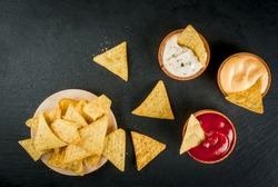 Snack for party, chips, nachos with sauces: tomato (ketchup), cheese and mayonnaise (tartar), top view, copy space