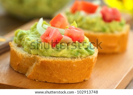 Snack of baguette slices with avocado cream, tomato and onion on wooden cutting board (Selective Focus, Focus on the front of the avocado cream on the first baguette slice)