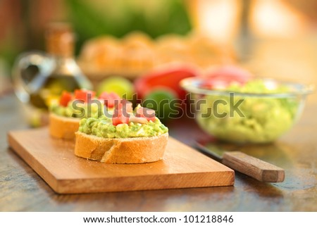 Snack of baguette slices with avocado-cream, tomato and onion on wooden cutting board with ingredients in back (Selective Focus, Focus on the front of the avocado-cream on the first baguette slice)