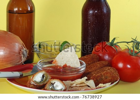 Snack plate filled with jalapeno poppers, salsa dip and tortilla chips and cold beer; plate surrounded by mexican food ingredients and yellow background.