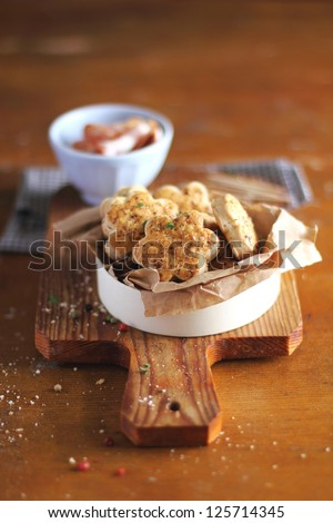 Snack scones or cookies with bacon, basil, maple syrup and peppercorns in a white box on a wooden cutting board with a bowl of bacon slices