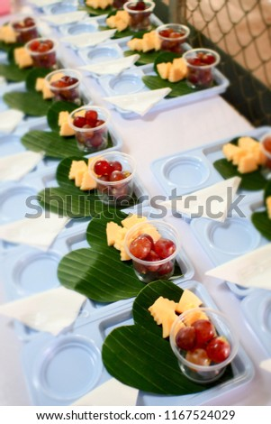 Snack set prepared for serve people who joined the meeting.Include fresh red grapes in plastic cup,delicious melon,all served in blue plate on green heart shaped banana leaves.Eco and reusable. #1167524029