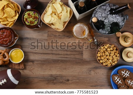 Snacks and drinks laid out for a football watching party. Top view with copy space.  #775581523