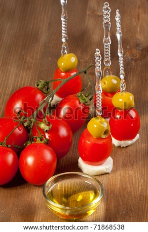 Snacks with green olives and fresh tomato on wooden table