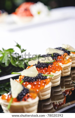 snacks with salmon roe and vegetables on a black plate