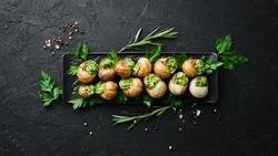 Snails baked with sauce. Baked snails with butter and spice. Top view. Free space for your text.