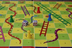 Snake and ladder game board with dice and piece. colorful snake and ladder. game board. dice and buttons. Moksha Patam. game board with numbers, gridded squares.