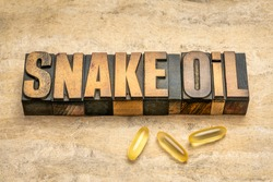 snake oil word abstract in vintage letterpress wood type, Chinese medicine or any cryptographic method or product considered to be bogus or fraudulent