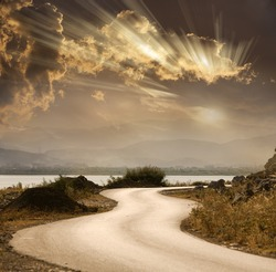 snake road under dramatic sky with sun rays