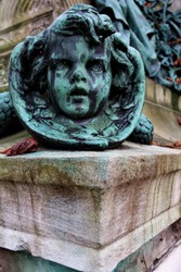 Snake with child's face on a grave. Old bronze sculpture.