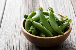 Snap peas in a wooden bowl set against an old wooden background