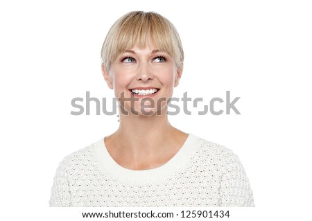 Snap shot of a smiling blonde looking upwards. Thinking something and smiling.