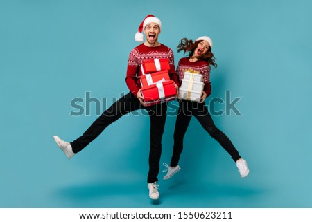 Snapshot of full-length jumping happy guy and girl in Christmas outfits. Couple in great mood posing with gifts on blue background