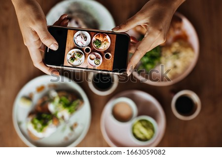Photo of  Snapshot of tanned female hands holding smartphone and taking photos of plate with meal. Picture of delicious colorful food on wooden table