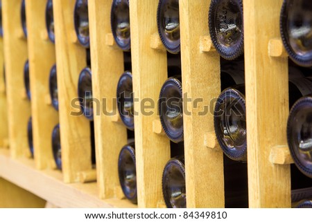 Snapshot of the wine cellar. The bottles on wooden shelves.