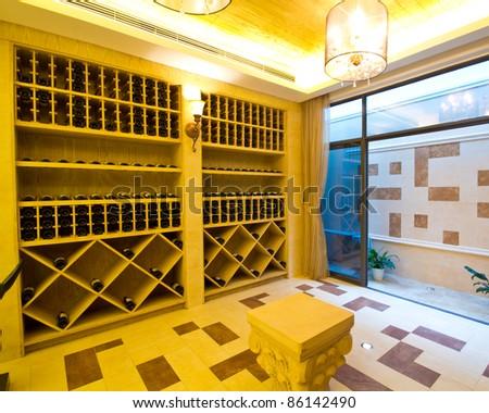 Snapshot of the wine cellar. The bottles on wooden shelves.