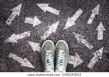 Sneaker shoes and arrows pointing in different directions on asphalt ground, choice concept #1340293052