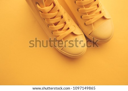 Sneaker shoes for youth lifestyle concept, pastel toned yellow footwear with copy space, top view #1097149865