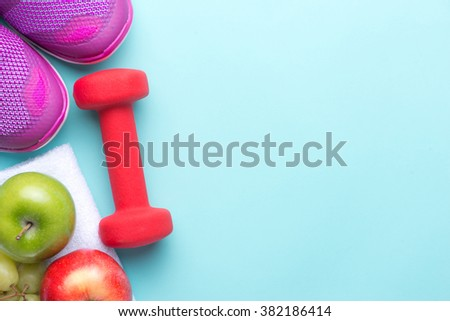 Sneakers and dumbbells fitness on a gray background. Different tools for sport. Sport shoes and water with set for sports activities on tiled floor.