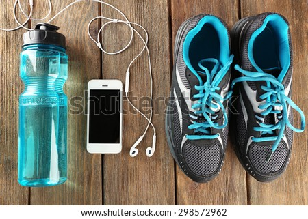 Sneakers and earphones on wooden table, top view