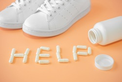 Sneakers and pills. capsules and sneakers. Word help is lined with capsules or pills on bright background. Supportive drugs for the activities and sneakers. Helps support joint health