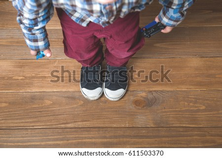 Sneakers on a kids feet. Children's shoes on a beach wooden background boardwalk