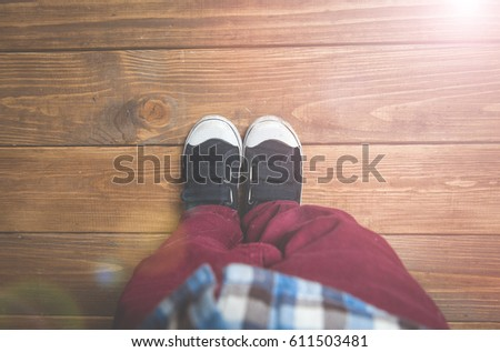 Sneakers on a kids feet. Children's shoes on a beach wooden background boardwalk