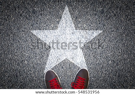 Sneakers on asphalt road with white star shape #548531956