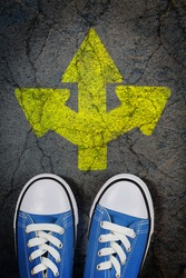 sneakers on cracked concrete surface with painted arrow pointing in three different directions