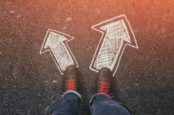Sneakers on the asphalt road with drawn arrows pointing in two directions. Making decisions and making choices concept.