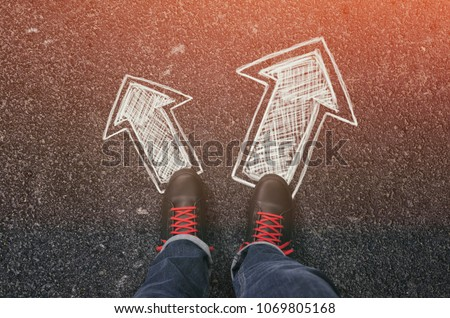 Sneakers on the asphalt road with drawn arrows pointing in two directions. Making decisions and making choices concept. #1069805168